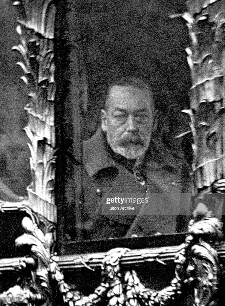 King George V (1865 - 1936) looking through the window of the ornate State Coach during the journey to Westminster for the ceremonial opening of Parliament.