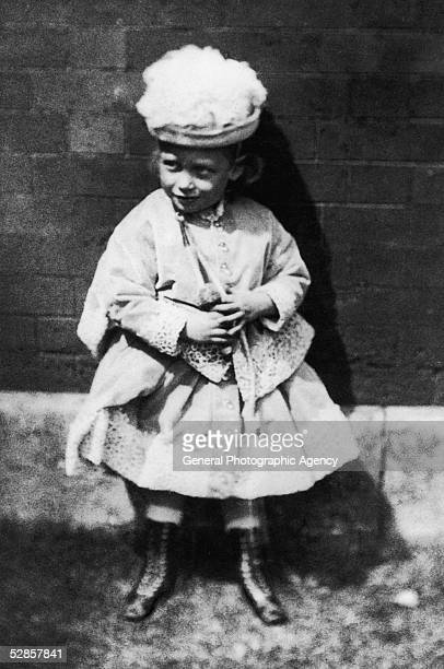King George V of Great Britain in girl's clothing as a child, circa 1868.