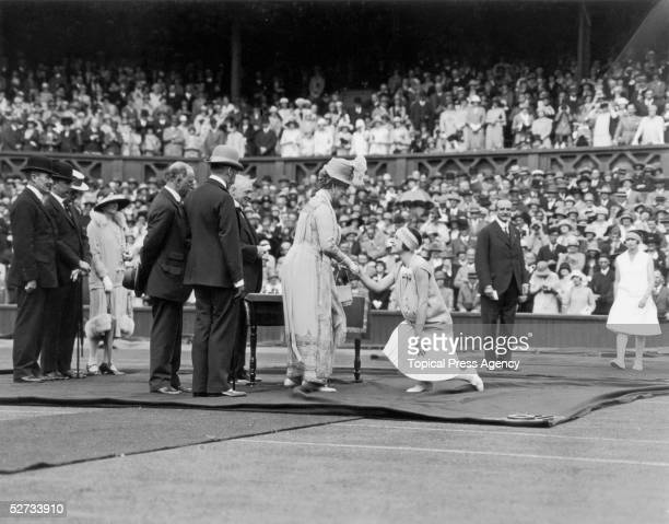 King George V opens Wimbledon's Jubilee Tennis Championships, June 1926. French player Suzanne Lenglen shakes the hand of royal consort Queen Mary.