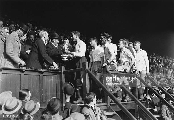 King George V presents the cup to Tottenham Hotspur captain Arthur Grimsdell after his team beat Wolverhampton Wanderers 1-0 to win the FA Cup Final...