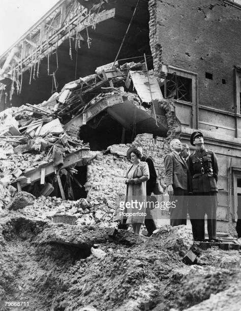 King George VI and Queen Elizabeth inspect the damage to a cinema building in Baker Street after it was destroyed by Nazi bombing in an air raid over...