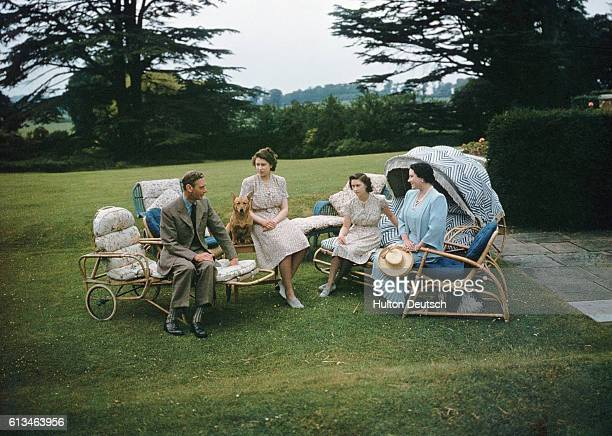 King George VI and Queen Elizabeth of England relax in the gardens of the Royal Lodge at Windsor with their daughters, Princess Elizabeth and...