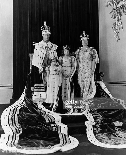 King George VI and Queen Elizabeth of England with their daughters Princess Elizabeth and Princess Margaret in their coronation robes