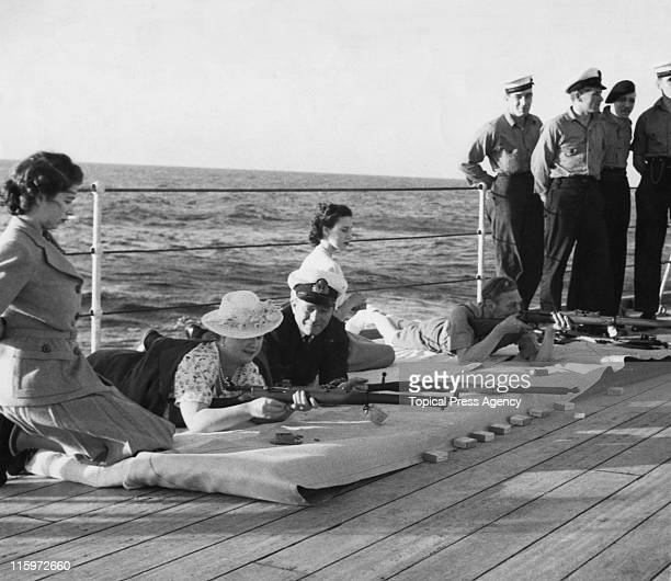 King George VI and the Queen Mother taking part in rifle shooting with the crew of HMS Vanguard, during the royal familiy's trip to South Africa,...