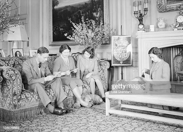 King George VI Queen Elizabeth and Princess Elizabeth sitting on a couch as Princess Margaret grooms a pet dog at the Royal Lodge in Windsor Castle...