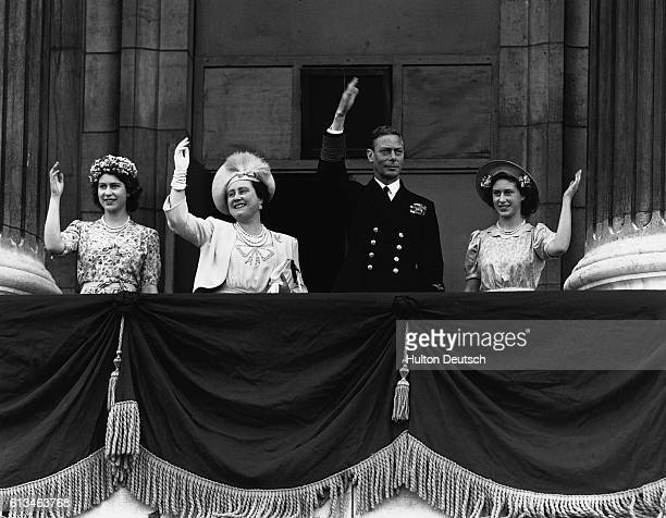 King George VI Queen Elizabeth and the princesses Elizabeth and Margaret wave happily from the balcony of Buckingham Palace on VJ Day August 15 1945...