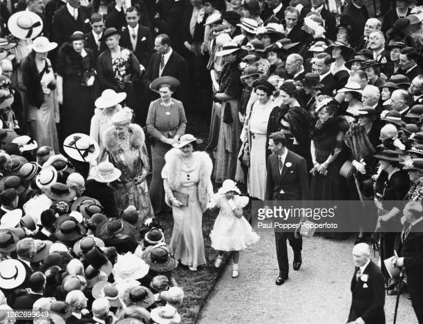 King George VI Queen Elizabeth Princess Margaret and Queen Mary of Teck attend a royal garden party held in the garden at Buckingham Palace in London...