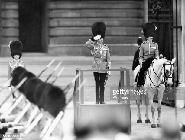 King George VI taking the salute from a dais at the centre gate at the guards march past in celebration of his official 53rd birthday