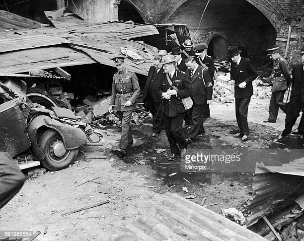 King George VI walks past a wrecked car on a walkabout in the East End of London following a Nazi air raid 10th September 1940