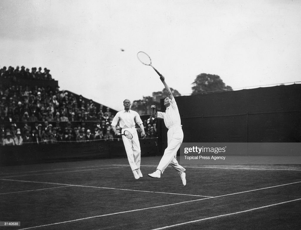 King George VI (1895 - 1952) when Duke of York reaches for an overhead shot during a tennis match at Wimbledon, his partner is Sir Louis Greig.
