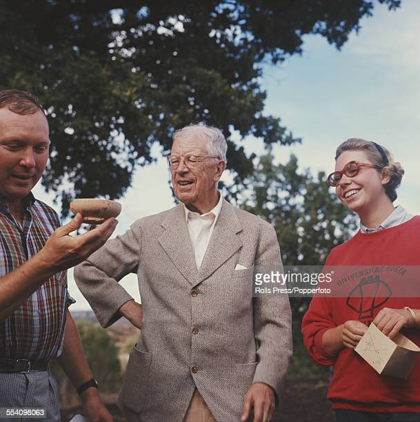 King Gustaf VI Adolf of Sweden pictured centre in his role as an amateur archaeologist looks at a piece of pottery just uncovered during excavations...