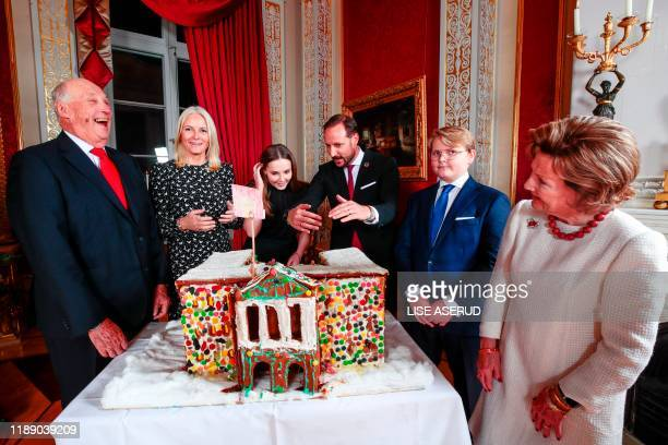 King Harald Crown Princess MetteMarit Princess Ingrid Alexandra Crown Prince Haakon Prince Sverre Magnus and Queen Sonja admire the gingerbread house...
