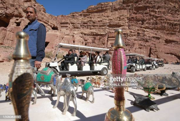 King Harald V of Norway and his wife Queen Sonja take a cart tour past a tourist gift stall during their visit of Jordan's archaeological city of...