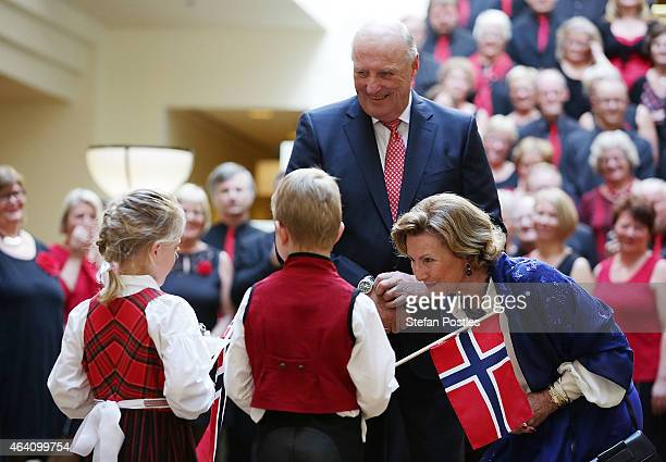 King Harald V of Norway and Queen Sonja of Norway receive flowers from children during a Norwegian Community Reception at the Hyatt Hotel on February...