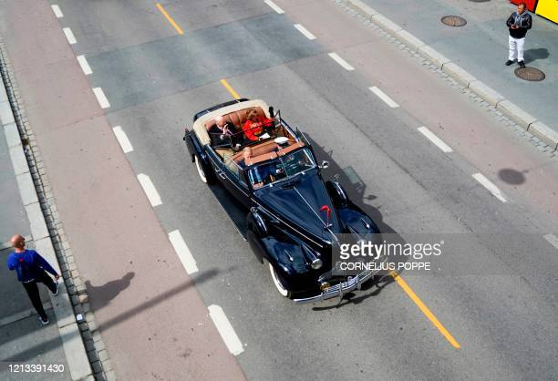 King Harald V of Norway and Queen Sonja of Norway sit in their old convertible car as they drive through the streets of Oslo during celebrations of...
