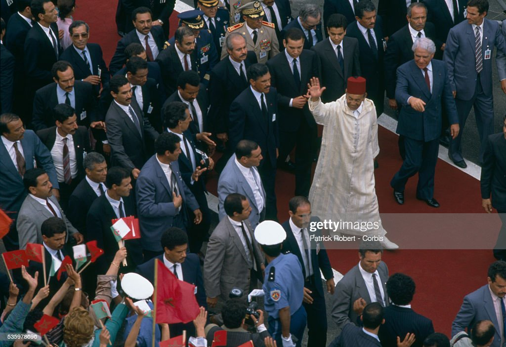King Hassan II of Morocco (waving) arrives in Algiers for the Algiers Summit. Algerian President Chadli Bendjedid (R) greeted him upon his arrival at the first North African economic summit to include leaders from Morocco, Algeria, Tunisia, Libya, and Mauritania.