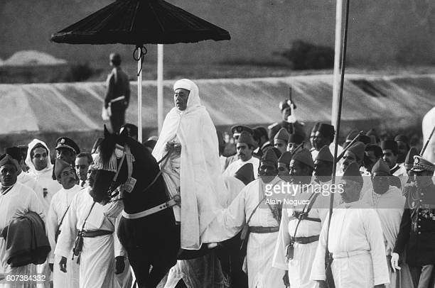 King Hassan II rides a horse during the ceremony.