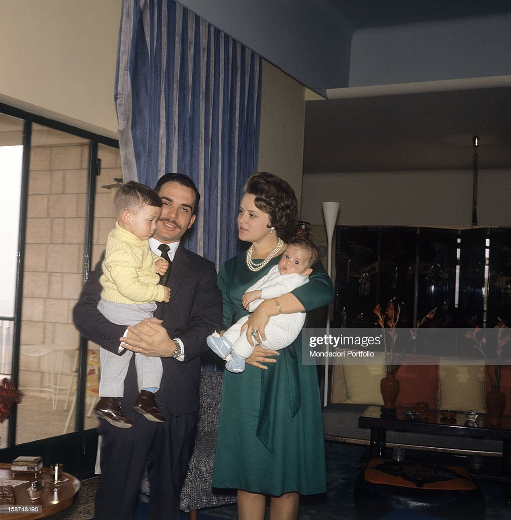 King Hussein of Jordan photographed in his house in Amman with his first son Abd Allah in arms, while his wife Muna is holding their second son, Faysal. Amman (Jordan), March 1964.