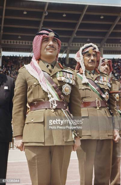 King Hussein of Jordan pictured standing to attention in full military uniform as he presents flags to new regiments at a Jordanian armed forces...