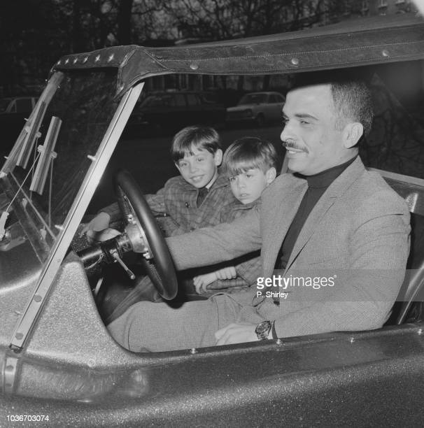 King Hussein of Jordan pictured with his two sons Prince Abdullah and Prince Faisal in a soft top car on a road in England on 7th December 1970