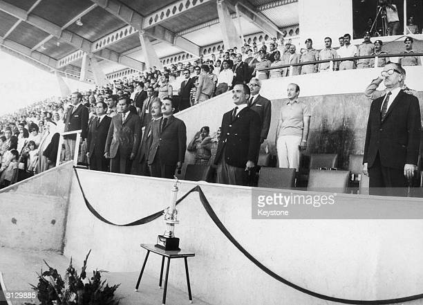 King Hussein of Jordan stands for the national anthem before a soccer match at the AlHussein Youth City stadium in Amman 2nd July 1969 On the king's...