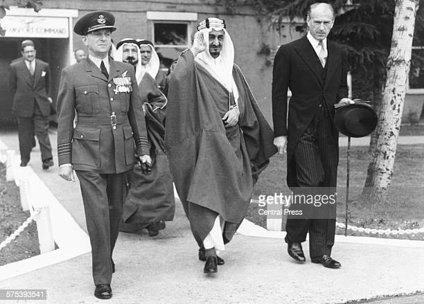 King Ibn Saud of Arabia with Marcus Chepke and Group Captain Hodgson walking to his aircraft after a state visit at Northolt Airport England August...