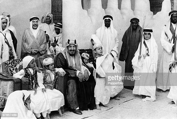 King Ibn Saud of Saudi Arabia with five of his sons and a group of palace servants Riyadh Saudi Arabia circa 1930