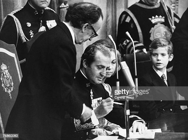 King Juan Carlos I of Spain signs the Spanish Constitution of 1978 at a special joint meeting of parliament in Madrid, establishing Spain as a...