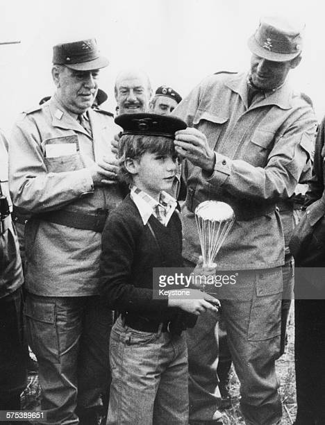 King Juan Carlos of Spain adjusting a parachutist bonnet on the head of his son, Prince Felipe, after it was presented to him by General Caillaud,...