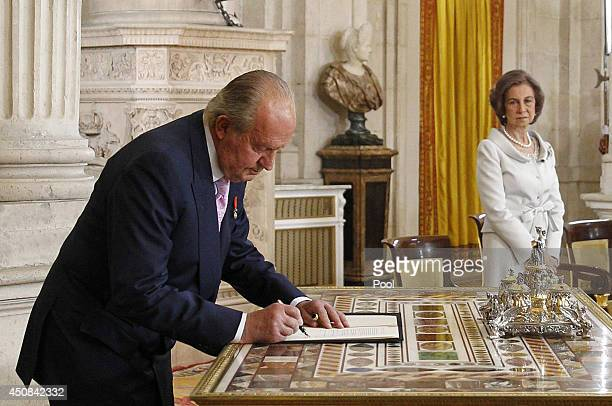 King Juan Carlos of Spain, in the presence of Queen Sofia of Spain, signs the abdication documents at the official abdication ceremony at the Royal...