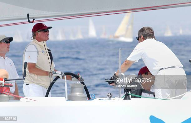 King Juan Carlos of Spain left steers a yacht during the first day of the 20th Copa del Rey regatta July 31 2001 at Palma de Mallorca Island Spain