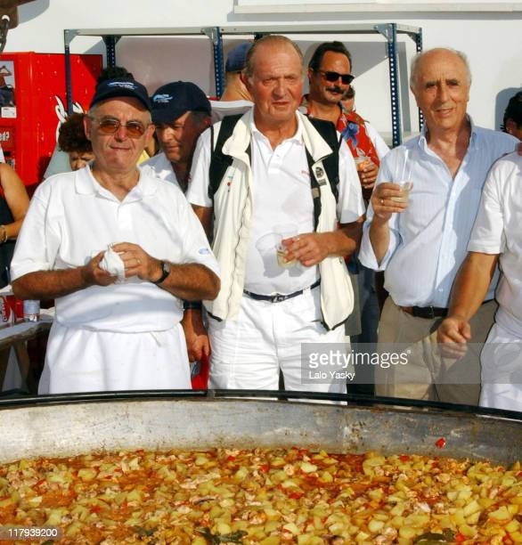 King Juan Carlos of Spain poses in front of a giant paella prepared to celebrate the completion of the 'Copa del Rey' Sailing Trophy in Mallorca