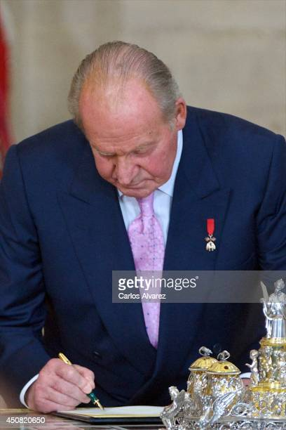 King Juan Carlos of Spain signs the official abdication papers at the Royal Palace on June 18 2014 in Madrid Spain