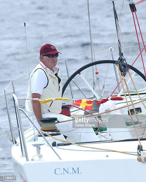 King Juan Carlos of Spain sits onboard the Bribon as he attends the third day of the 21st sailing event known as the Copa del Rey July 31 2002 in...
