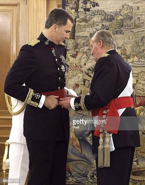 King Juan Carlos places the sash of the captain general of the armed forces on his son King Felipe VI of Spain in a ceremony held in the Hearing Room...