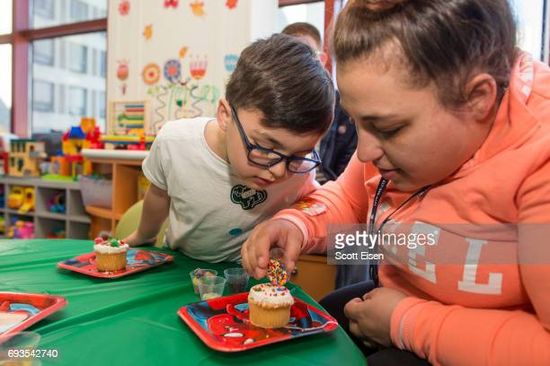 King left and mom decorating cupcakes at a party in honor of Eversource's longstanding commitment of Boston Children's Hospital on June 7 2017 in...