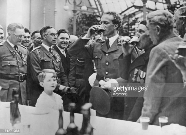 King Leopold III of Belgium has a drink at the buffet whilst Prince Baudouin looks on The party is being given by the King at the Royal Palace of...