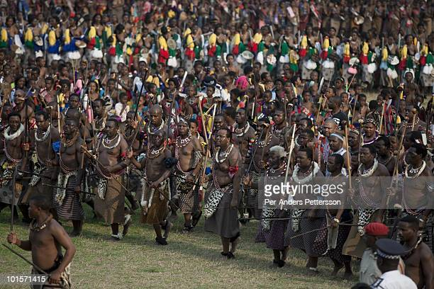 King Mswati III dances with his men in front of young virgins at a traditional Reed dance ceremony at the stadium at the Royal Palace on August 31 in...