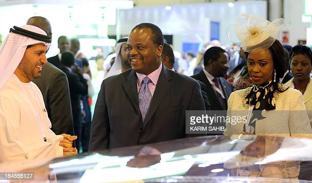 King Mswati III of Swaziland and his wife Inkhosikati LaMbikiza listen to a presentation by an exhibitor during the opening of the World Energy Forum...