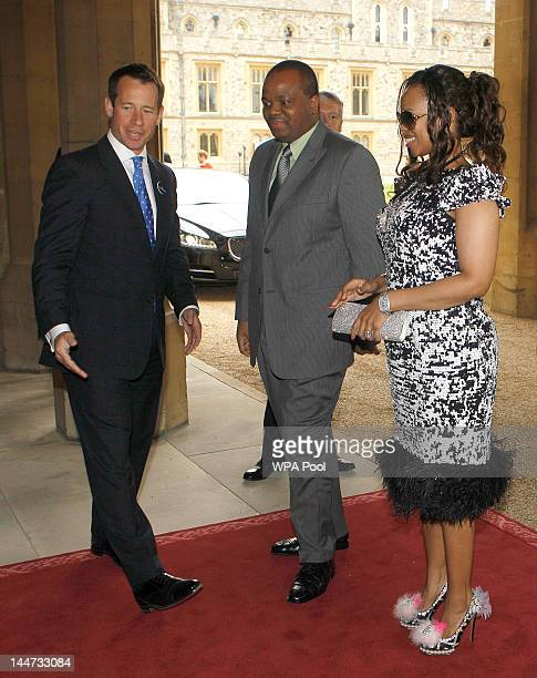 King Mswati III of Swaziland and Inkhosikati LaMbikiza are greeted by household staff as they arrive at a lunch For Sovereign Monarchs in honour of...