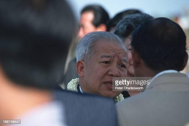 King Norodom Sihanouk greets dignitaries on his arrival at Pochentong Airport..