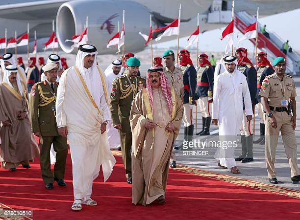 King of Bahrain Hamad bin Issa alKhalifa welcomes the Emir of Qatar Sheikh Tamim bin Hamad alThani upon his arrival for the 37th Gulf Cooperation...
