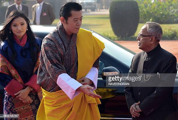 King of Bhutan, Jigme Khesar Namgyel Wangchuk shakes hands with Indian President Pranab Mukherjee as Bhutanese Queen Jetsun Pema Wangchuck looks on...