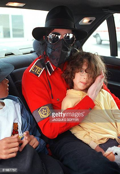 US King of Pop Michael Jackson with his face covered with a scarf and wearing sun glasses holds 13 May 1993 an unidentified child while accompanied...