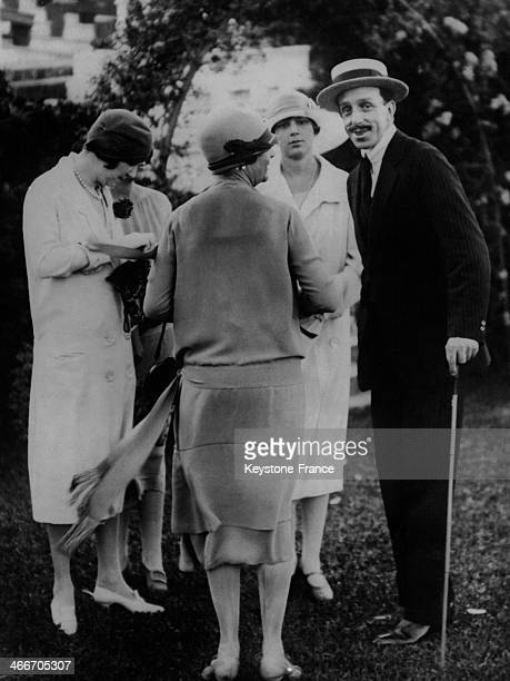 King of Spain Alfonso XIII and his daughter Infanta Beatriz attend a garden party given by the Duchess of Fernan Nunez at her residence circa 1930 in...