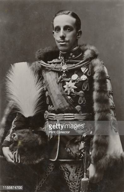 King of Spain', circa 1910. Portrait of Alfonso XIII , King of Spain, wearing a fur-lined cape and holding a plumed helmet. The posthumous son of...