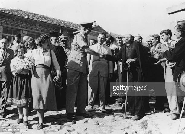 King Paul and Queen Frederika of Greece surrounded by a crowd of people as they inaugurate a new nursery in the village of Avgerinos, Macedonia, July...