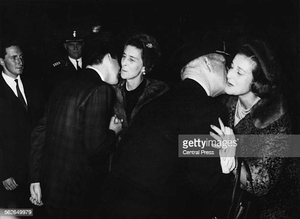 King Paul of Greece kissing the cheek of Princess Alexandra and Crown Prince Constantine kisses the cheek of Princess Marina as the princesses arrive...