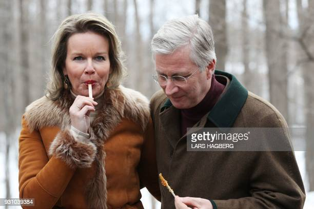 King Philippe and Queen Mathilde of Belgium try freshly made maple taffy during a visit to Richelieu Park Sugar Shack in Ottawa Ontario on March 12...