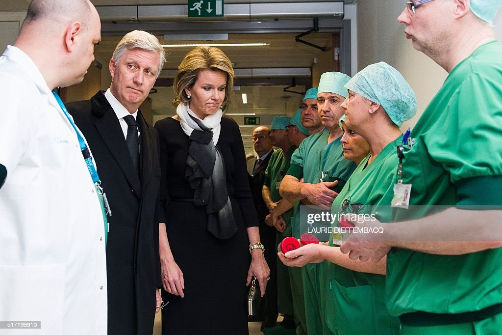 King Philippe - Filip of Belgium (2nd L) and Queen Mathilde of Belgium meet with medical staff at the 'Campus Gasthuisberg UZ' hospital in Leuven, outside Brussels, on March 24, 2016 during their visit to the injured victims of the Brussels attacks, two days after a triple bomb attack, which responsibility was claimed by the Islamic State group, hit Brussels' airport and the Maelbeek - Maalbeek subway station, killing 31 people and wounding 270 others. Belgian authorities are seeking a second suspect over the attack on a metro train in Brussels in which one suicide bomber has already been confirmed dead, police sources told AFP on March 24. / AFP / Belga / LAURIE DIEFFEMBACQ / Belgium OUT
